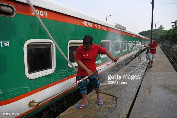 Railway workers are seen washing a train at Komlapur railway station as the train service prepares to resume. The intercity train will resume...