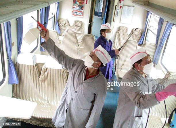 Railway workers disinfecting a soft-sitter cabin of a train, prior to passengers boarding at the Jinan Railway station in northeastern Shandong...