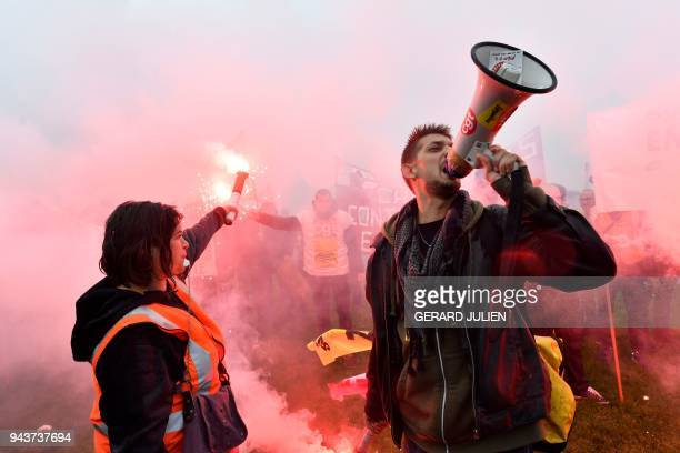 TOPSHOT SNCF railway workers hold flares and chant slogans as they demonstrate as part of their strike over plans to overhaul the national stateowned...