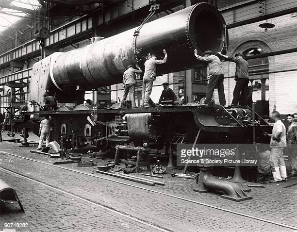 Railway workers lower the boiler into the frame of the first London Midland Scottish Railway 462 steam locomotive no 6200 Photograph by a Derby Works...
