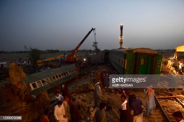 Railway workers operate at the site of a train accident in Daharki area of the northern Sindh province on June 7 as at least 43 people were killed...