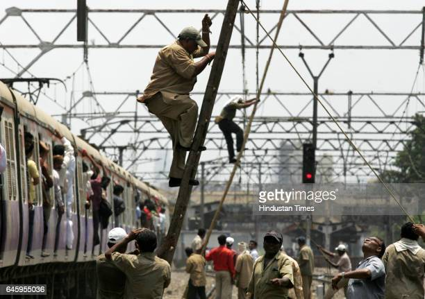 Railway workers repair overhead wire which was snapped between at between Khar and Santacruz on Friday