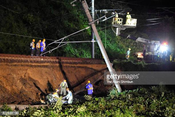 Railway workers survey the extent of rain damage to the rail foundation of the JR Ou Line which is also used by the Akita Shinkansen near...