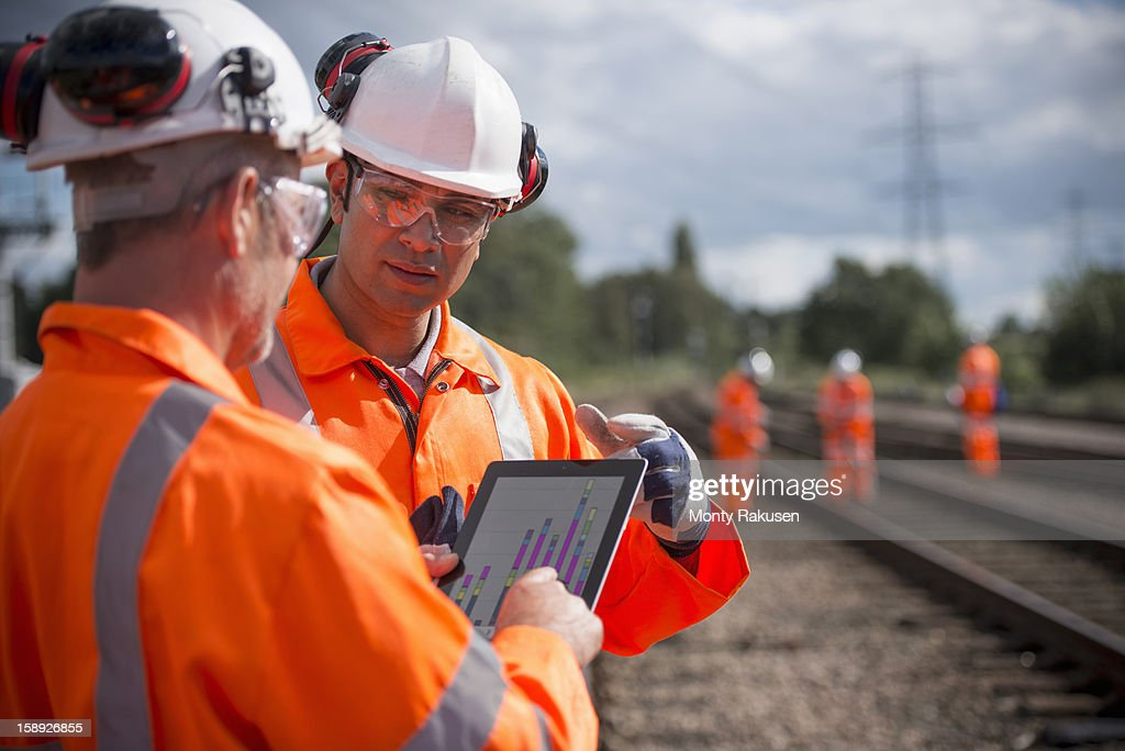 Railway workers using digital tablet to discuss work : Stock Photo