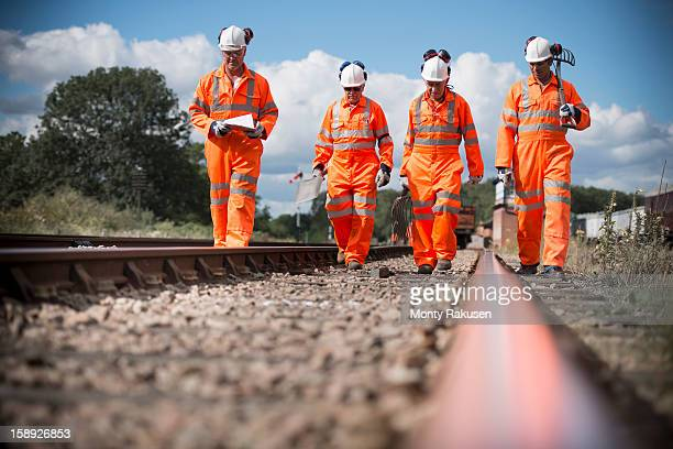 Railway workers walking down and checking tracks, front view