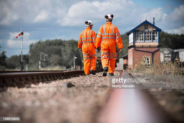 Railway workers walking down and checking tracks, rear view