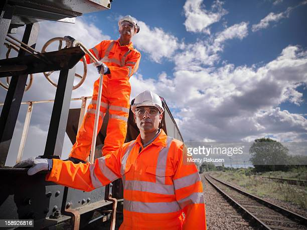 Railway workers wearing high visibility clothing on train
