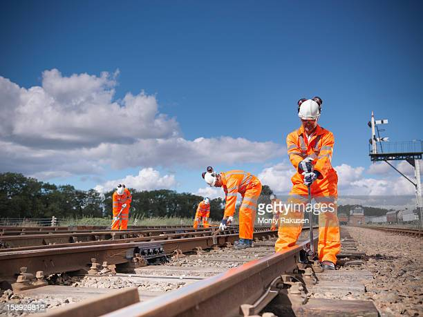 railway workers wearing high visibility clothing repairing railway track - rail transportation stock pictures, royalty-free photos & images