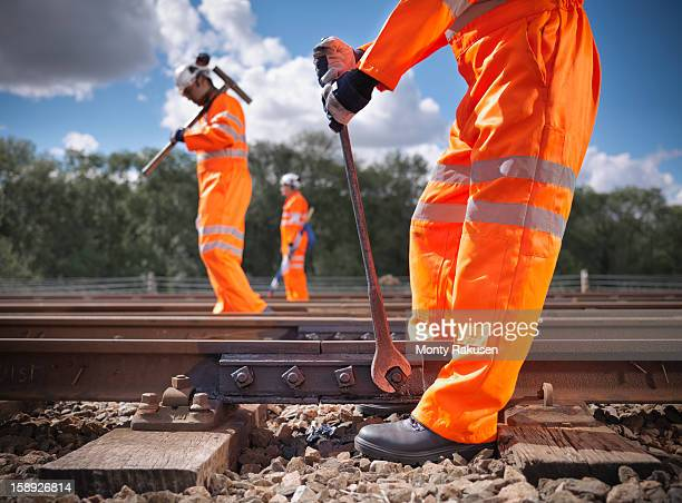 railway workers wearing high visibility clothing repairing railway track side view - tighten stock photos and pictures