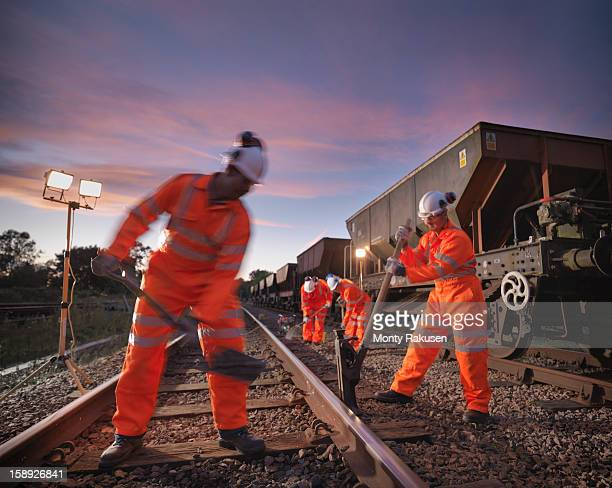 Railway workers with spade and tools working on railway tracks at night