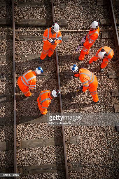 Railway workers working on railway tracks, overhead view