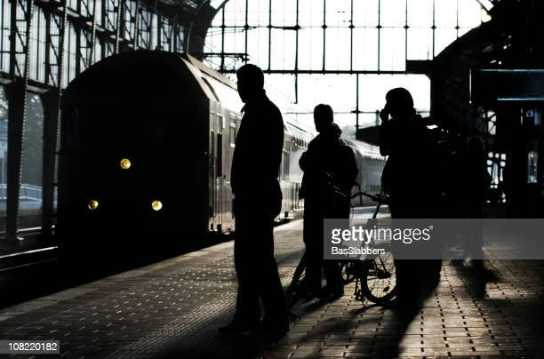 railways; silhouette of people standing on platform while train arrives - basslabbers, bastiaan slabbers stock pictures, royalty-free photos & images