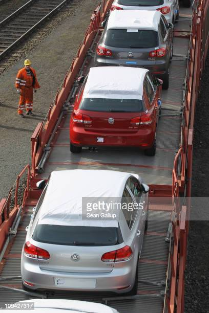 A railways worker watches as a train loaded with new Volkswagen Golf Tiguan and Touran cars rolls past at the Volkswagen factory on February 25 2011...