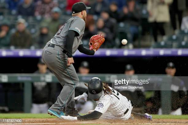 Raimel Tapia of the Colorado Rockies scores on a wild pitch in the fourth inning against Merrill Kelly of the Arizona Diamondbacks at Coors Field on...