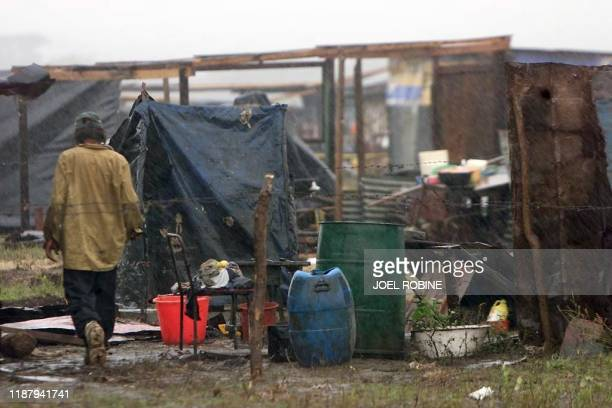 Rain beats down 09 November on the New Life Quarter a camp of plastic sheeting and shacks installed at Ciudad Sandino 15 kilometers from Lake Managua...