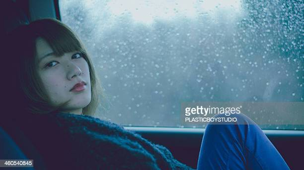 Rain / car / window / woman / bored / grumpy