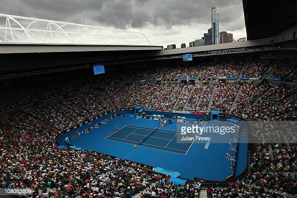 Rain clouds are seen over the Rod Laver Arena as Roger Federer of Switzerland plays in his first round match against Lukas Lacko of Slovakia during...