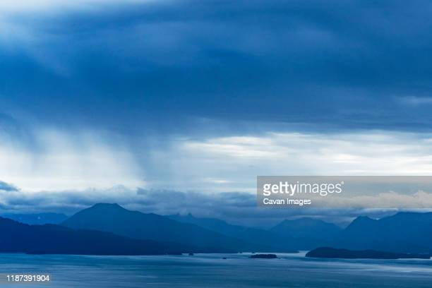 rain clouds form with mountains in the distance in kachemak bay - kachemak bay stock pictures, royalty-free photos & images