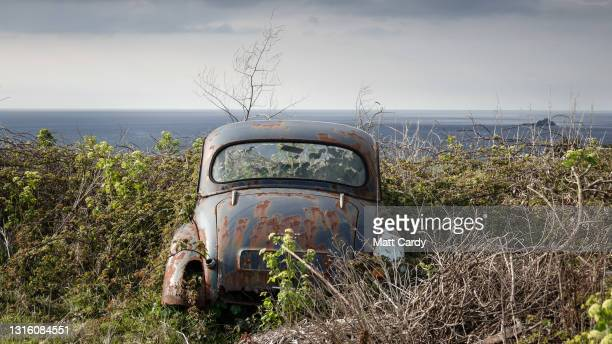 Rain clouds gather above a rusty old Morris Minor car left in a field above Sennen Cove on April 17, 2021 in Cornwall, England. With international...