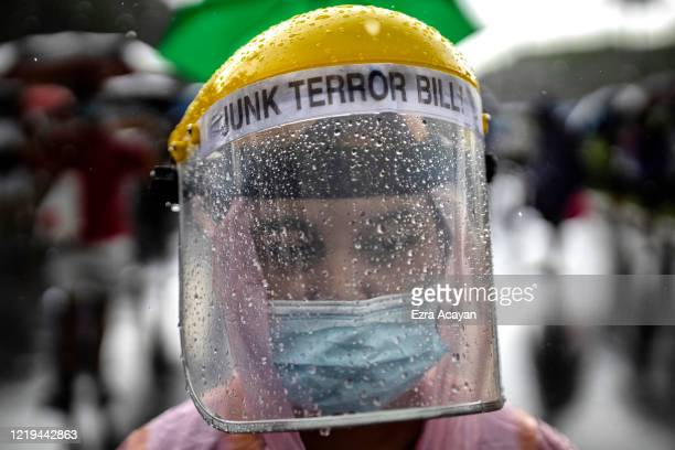 Rain droplets are seen on a woman's face shield as she takes part in a protest against President Duterte's Anti-Terror bill on June 12, 2020 in...
