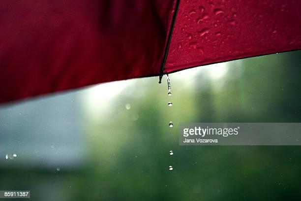Rain drops falling from red umbrella
