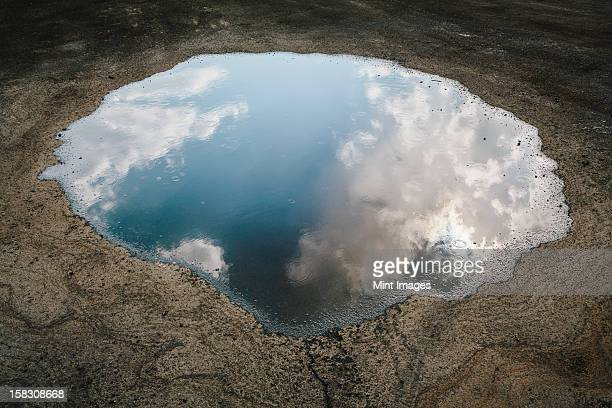 rain drops falling onto a large puddle. a reflection of sky and clouds. - puddle stock pictures, royalty-free photos & images