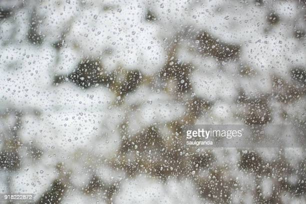 Rain drops on a glass with snow in the background