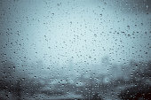 Rain drops on window glass outside texture background water of wonderful heavy rainy day with sky clouds at city blue green blurred lights abstract view sunshine enjoy the relaxing nature wallpaper