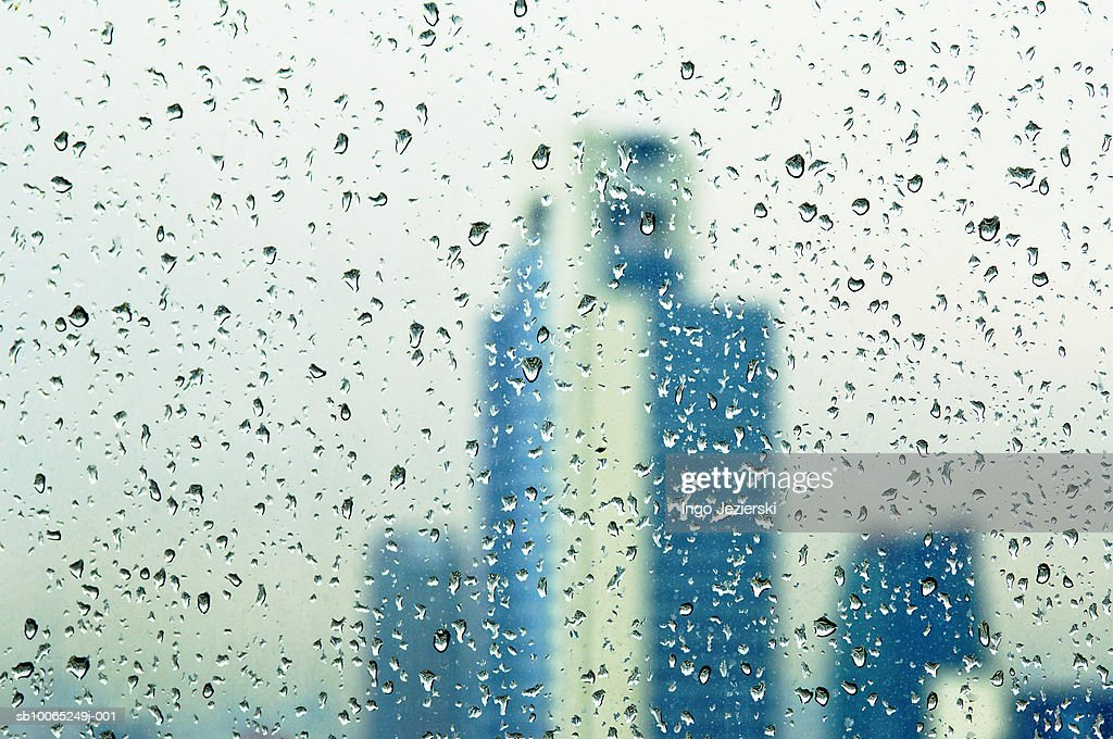 Rain drops on window, out of focus buildings in background : Foto stock