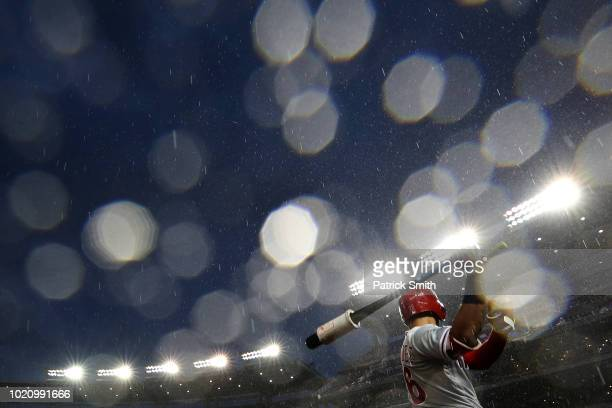 Rain falls as Cesar Hernandez of the Philadelphia Phillies prepares to bat against the Washington Nationals during the third inning at Nationals Park...