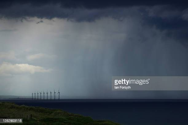 Rain falls near an offshore windfarm as a thunderstorm approaches overhead on June 27, 2020 in Saltburn By The Sea, England. Thunderstorms have...