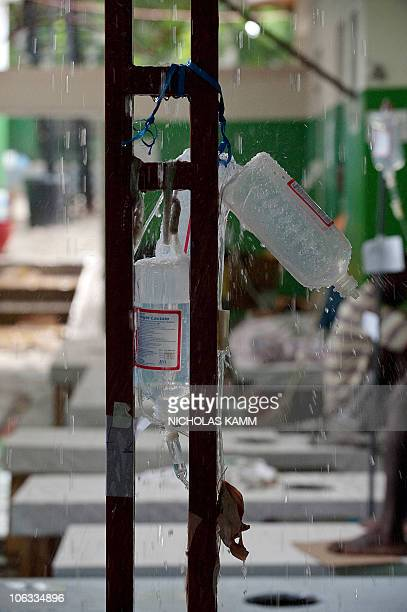 Rain falls through the roof on IV drips in a ward of cholera patients at the Charles Colimon Hospital in Petite Riviere on the Artibonite River...