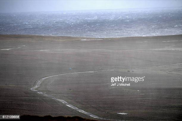 Rain moves across the main arterial road on the Island of Foula on September 29 2016 in Foula Scotland Foula is the remotest inhabited island in...