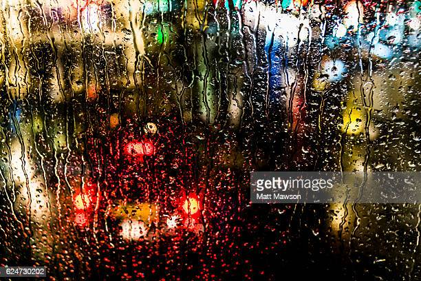 Rain on a car windscreen and city lights reflecting on a wet street