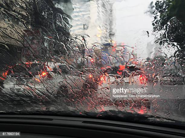 Rain on car windshield and illuminated taillights seen from inside car