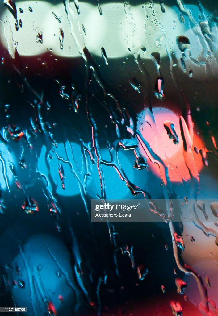 rain on the glass with colored reflections : Stock Photo