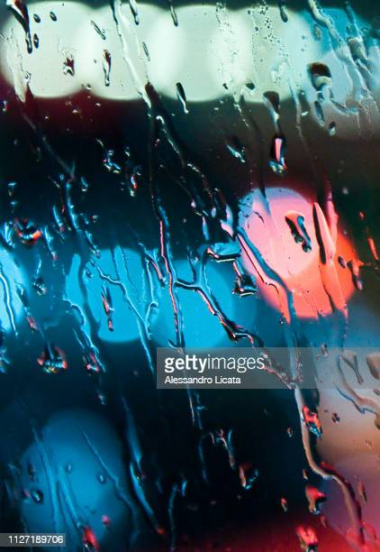 rain on the glass with colored reflections - bagnato imagens e fotografias de stock