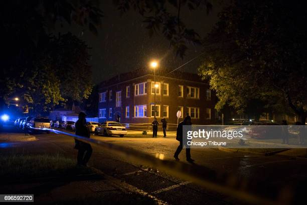 Rain pours down as Chicago Police officers work at the scene of a fatal shooting in the 5900 block of West Thomas Street Friday June 16 in the Austin...