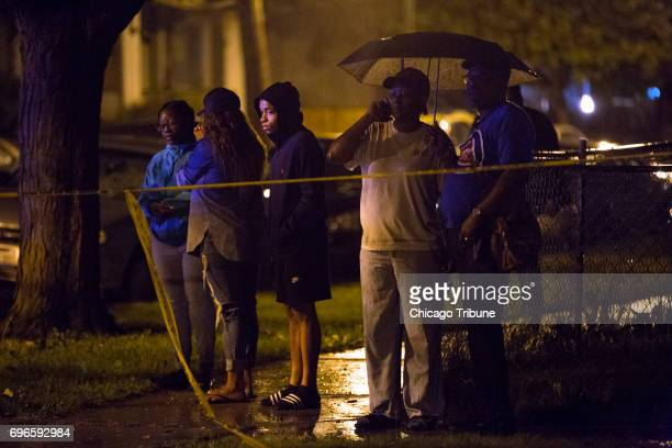 Rain pours down as people stand at the scene of a fatal shooting in the 5900 block of West Thomas Street Friday June 16 in the Austin neighborhood of...