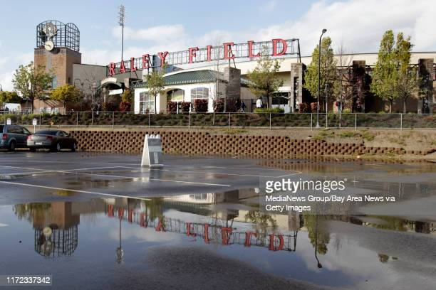 Rain puddles cover a parking lot as the Sacramento River Cats host the Oakland Athletics in an exhibition game at Raley Field in Sacramento, Calif.,...