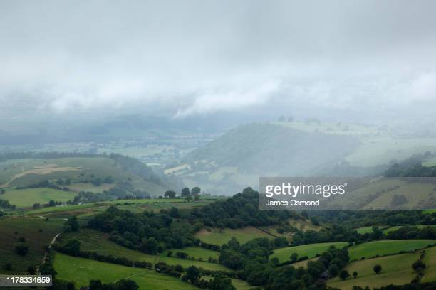 rain shower passing over fields, hills and woodland. - hill stock pictures, royalty-free photos & images