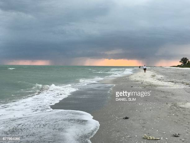 Rain showers are seen in the sunset on Sanibel Island beaches west of Florida on April 19 2017 / AFP PHOTO / Daniel SLIM
