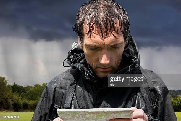 Regen eingeweicht Wanderer Blick in die Karte