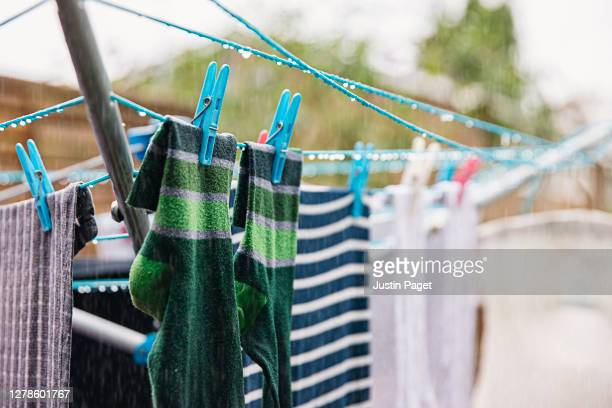 rain soaked laundry hanging on a clothesline in back garden - wet stock pictures, royalty-free photos & images