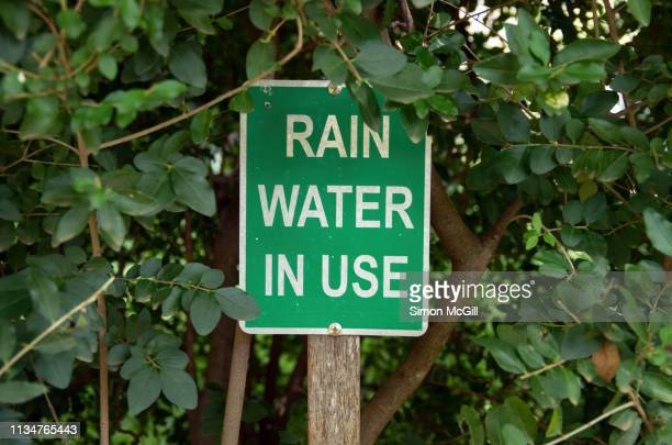 'rain water in use' sign on the perimeter of a suburban garden - water conservation stock pictures, royalty-free photos & images