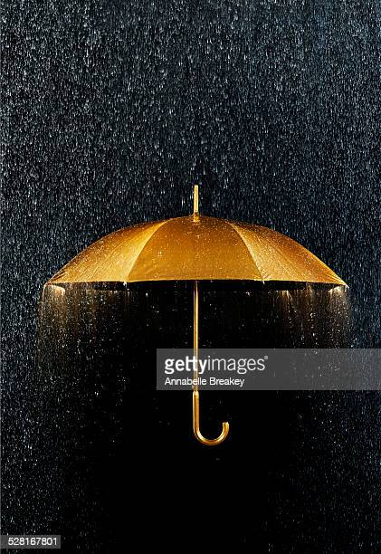 rain with gold umbrella - protection stock pictures, royalty-free photos & images