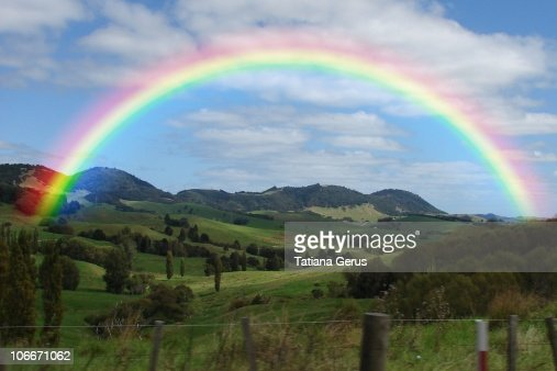rainbow above the valley new zealand stock photo