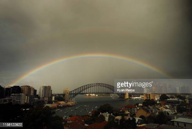 A rainbow and rain clouds are seen over the Sydney Harbour Bridge on June 25 2019 in Sydney Australia More than 30mm of rain has fallen across Sydney...