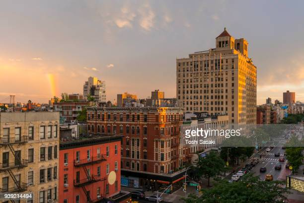 rainbow appears behind the rows of buildings during the dusk at east village manhattan new york, ny, usa - july 01 2017. - east village stock pictures, royalty-free photos & images