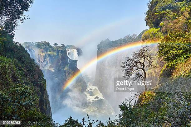 a rainbow appears in the gorge of victoria falls - victoria falls stock pictures, royalty-free photos & images
